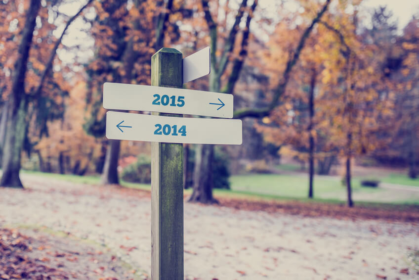 Signpost in a forested area with arrows pointing two opposite directions towards year 2014 and 2015.